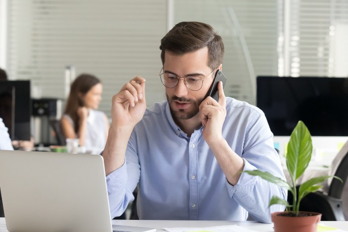 Marketing sales manager consulting client making offer selling talking on phone near laptop in office